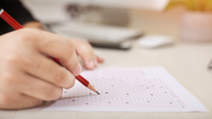 ręka ucznia wypełniającego czerwonym ołówkiem test