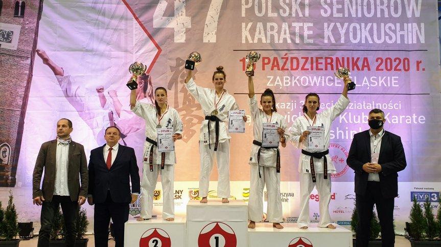 Zdjęcie przedstawia 4 zawodniczki karate stojące na podium