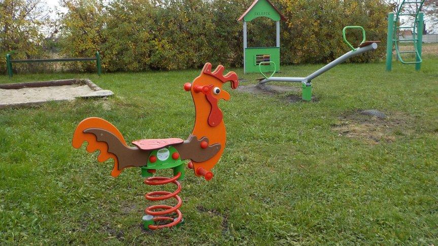 Trzy urządzenia zabawowe: pomarańczowy sprężynowiec kogut, zielona huśtawka wagowa, zielony sklepik z liczydłem.