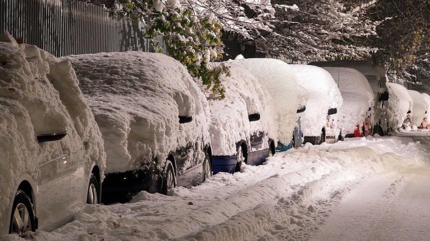 Pokryte grubą warstwą śniegu samochody zaparkowane wzdłuż krawędzi jezdni