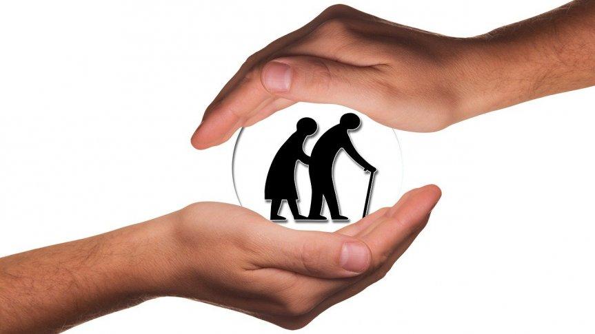 dwie dłonie osłaniają dwie osoby starsze