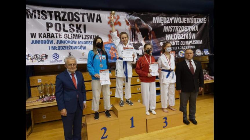 małgorzata biegańska na podium wraz z 3 zawodniczkami karate i dwoma sędziami