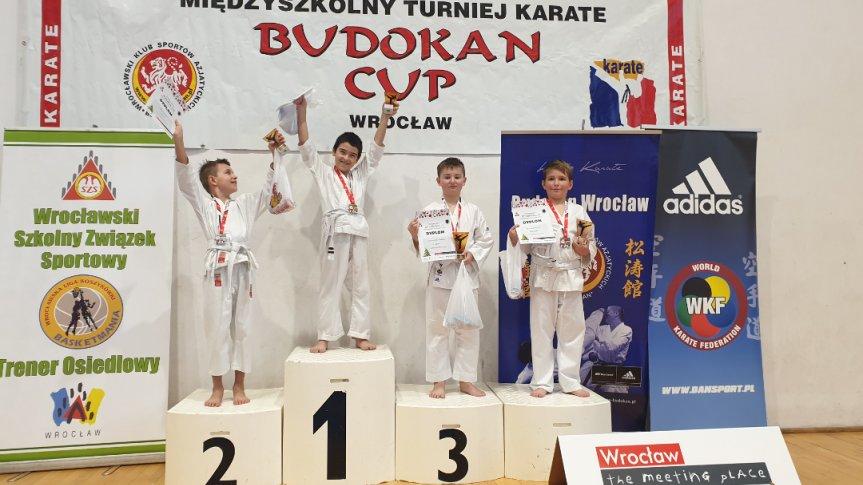 czwórka chłopców stojąca na podium. Są ubrani w stroje do karate.