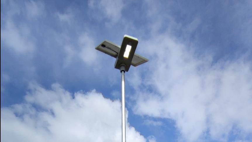 lampa fotowoltaiczna na tle niebieskiego nieba z niewielkim zachmurzeniem
